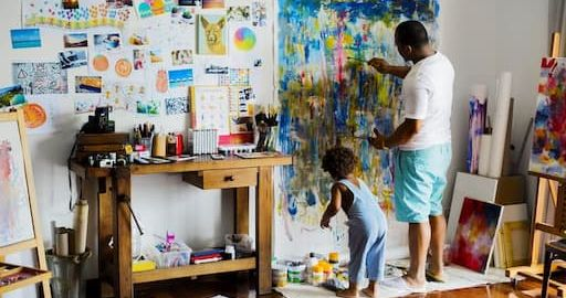 Artist dad painting a canvas with his son
