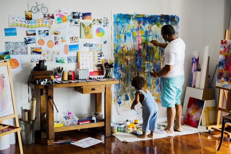 Artist father painting canvas with his young son