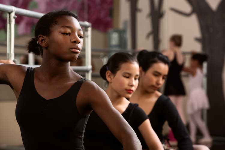 Three young ballet dancers at barre