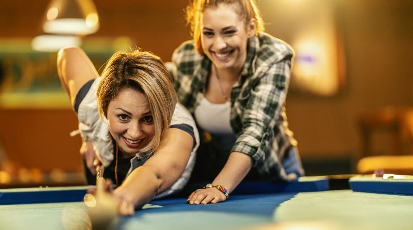 Two woman play billiards in a casual bar
