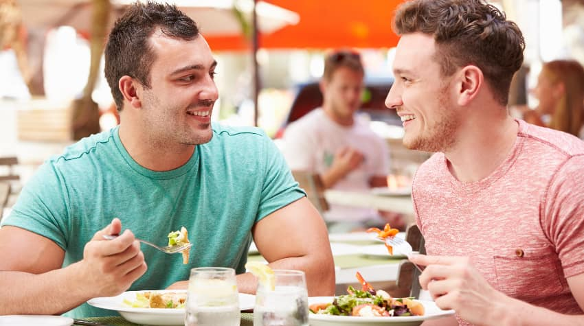 Two men smile and enjoy a meal on an outdoor patio