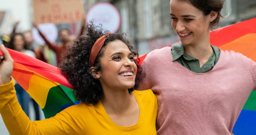 Two women hold a rainbow pride flag and march in a parade