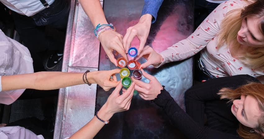A group of cheers toast a round of rainbow-colored shots at a bar