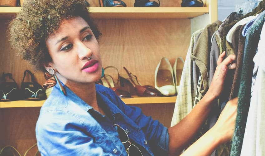 A woman in trendy clothes searches a clothing rack at a thrift store