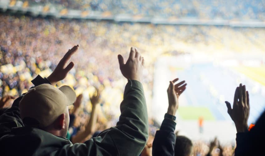 A close up fans cheering at a sporting event