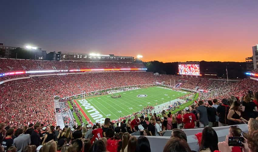 A UGA vs Notre Dame football game with a packed stadium in the evening