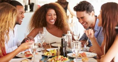 friends smile around a table filled with food