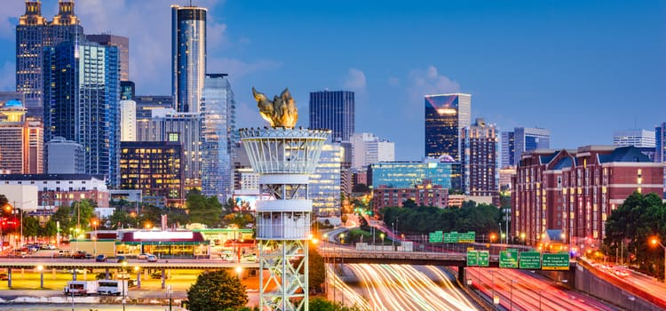 a view of the atlanta skyline at dusk, with the olympic torch sculpture in the forefront