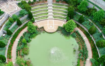 a large circular fountain with green-tinted water surroundd by trees and a pavement
