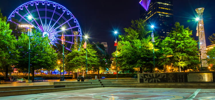 an open fountain area at centennial olympic park after dark, with the lit ferris wheel in the background