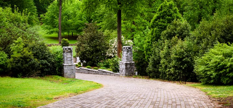 a stone-paved path lined with two stone columns leading into a green area with lots of trees at grant park
