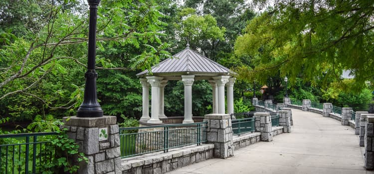 a small gazebo off of a paved trail lined with stone at piedmont park