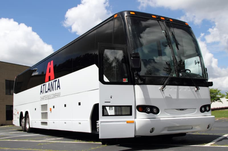 A branded Atlanta Charter Bus Company charter bus parks in an empty lot